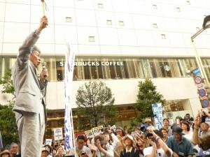 「非核都市宣言 憲法をまもり 平和を」と書かれたプラカードを掲げ、語りかける鳥越俊太郎都知事候補。7月24日
